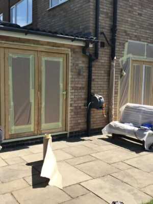 Masking the exterior house doors ready for painting their new colour